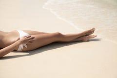Kvinnors sexiga ben på stranden Arkivfoton