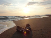 Kvinnors skor på sanden Arkivfoto