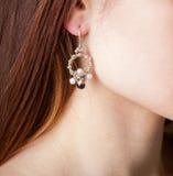 Kvinnors smycken, örhängen, halsband, en ung kvinna med en prydnad som är handgjord royaltyfri foto