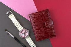 Kvinnors tillbehör, röd affärskorthållare, armbandsur, makeupborste på färgrika bakgrunder royaltyfri fotografi