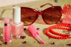 Kvinnors tillbehör: solglasögon kantglans, spikar polermedel, pärlor Arkivfoton