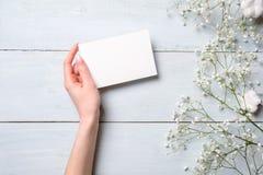 Kvinnors tomt pappers- kort för handinnehav på ljust - blå träbakgrund Lantlig tabell med blommor som gifta sig inbjudankortet, b royaltyfri bild