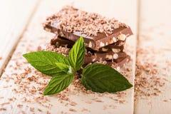 Kvist av mintkaramellen framme av chokladbunten på det vita brädet arkivbild