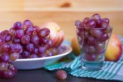 Kvistar av druvor i en platta och druvor i ett exponeringsglas och äpplen på royaltyfri foto