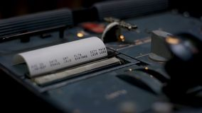 kvitto kontant illustrerande spenderat pengarkvitto Closeup av händer som räknar på en kassaapparat på mörk bakgrund Arkivbilder
