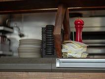 Kvitton som staplas upp med portionbunkar och plattor som sitter på en restaurangdiskbänk arkivbild