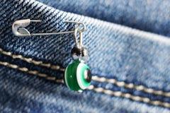 Kwaad oog op een speld op jeans stock afbeelding