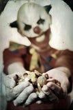 Kwade clown die suikergoed aanbieden aan de waarnemer royalty-vrije stock foto