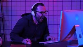 Kwade lough van boze gamer terwijl het spelen op de computer Emotionele gamer stock foto