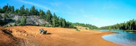 Kwadrata ATV stojaki na piaskowatym terenie przy pięknym jeziorem Obrazy Royalty Free