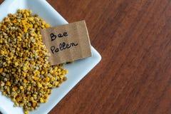 Kwadratowy spodeczek pełno troszkę pszczoły pollen z etykietką, na ciemnym drewnianym stole fotografia royalty free