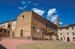 Kwadratowy widok kościół Sant ` Agostino z ludźmi w San Gimignano Obraz Stock
