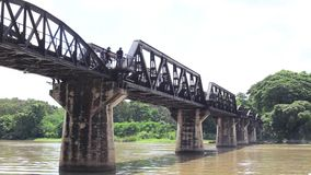 Kwai river bridge, Kanchanaburi, Thailand. From below at river bank showing concrete supports stock video