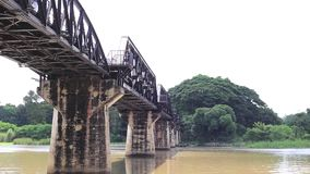 Kwai river bridge, Kanchanaburi, Thailand. From below at river bank showing concrete supports stock video footage