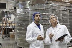 Kwaliteitscontrolearbeiders die bij bottelarij inspecteren Stock Fotografie