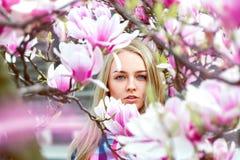 Kwam de hogere kringen blonde dame die in roze bloeiende bloemen bekijken royalty-vrije stock afbeelding