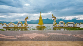 Kwan Phayao. Golden pagoda surrounded by 2 figures of naga with the sky, white cloud, sunlight and mountain in Phayao lake (Kwan Phayao) as background. This Stock Image