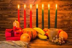 Kwanzaa-Feiertagskonzept mit traditionellen brennenden Kerzen, Geschenkbox, Stockfoto