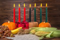 Kwanzaa festival concept with seven candles red, black and green. Gift box, pumpkins, ears of wheat, grapes, corns, banana, bowl and fruits on wooden stock photography