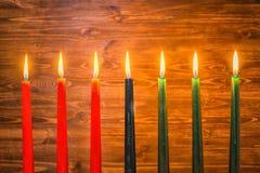 Kwanzaa festivalbegrepp med som sju stearinljus är röda som är svarta och grönt Arkivfoton