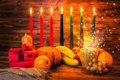 Kwanzaa holiday concept with traditional lit candles, gift box,. Pumpkins, ears of wheat and miracle magic light on wood background royalty free stock photos