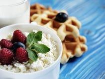 Kwark met bessen, wafels en melk op houten blauwe B Stock Foto