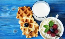 Kwark met bessen, wafels en melk op houten blauwe B Royalty-vrije Stock Foto's