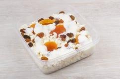 Kwark met droge abrikozen, rozijnen en yoghurt in conta Royalty-vrije Stock Foto's