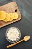 Kwark met sinaasappel op scherpe raad met houten lepel Stock Afbeelding