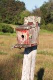 Kwartdraaimening van een oud vogelhuis met schilverf en mos Royalty-vrije Stock Foto