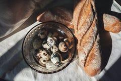 Kwartelseieren op een plaat en een brood Stock Fotografie