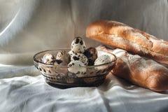 Kwartelseieren op een plaat en een brood Royalty-vrije Stock Foto
