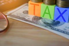 Kwekend belastingen - Close-up van kleurenblokken met BELASTING en geld op t Stock Fotografie