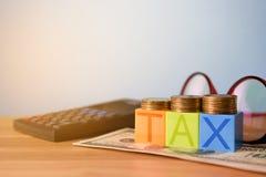 Kwekend belastingen - kleurenblokken met BELASTING en geld op lijst - Belasting Stock Afbeeldingen