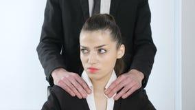 kwelling De leider in een kostuum maakt tot een schoudermassage aan zijn secretaresse 60 fps stock video