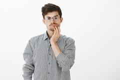 Kwestionujący wątpliwy atrakcyjny brodaty facet z wąsem w round szkłach trzyma rękę na podbródku i patrzeje w dół, podczas gdy zdjęcia royalty free