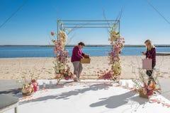 Kwiaciarni decorator obieg, kobieta dekoruje ślubny łuk z świeżymi kwiatami Wydarzenie dekoracja z świeżymi kwiatami obrazy royalty free