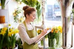 Kwiaciarni kobieta z schowkiem przy kwiatu sklepem Zdjęcia Royalty Free