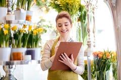 Kwiaciarni kobieta z schowkiem przy kwiatu sklepem Zdjęcie Royalty Free
