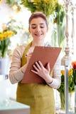 Kwiaciarni kobieta z schowkiem przy kwiatu sklepem Fotografia Royalty Free