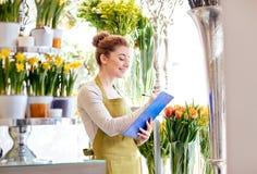 Kwiaciarni kobieta z schowkiem przy kwiatu sklepem Obrazy Stock