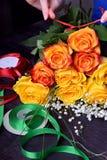 Kwiaciarnia komponuje bukiet żółty i pomarańczowe róże i łyszczec kwitną zdjęcie stock