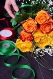 Kwiaciarnia komponuje bukiet róże i łyszczec kwiat żółte i pomarańczowe zdjęcia royalty free