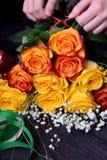 Kwiaciarnia komponuje bukiet róże i łyszczec kwiat żółte i pomarańczowe zdjęcie stock