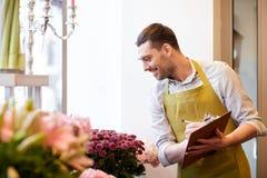 Kwiaciarnia mężczyzna z schowkiem przy kwiatu sklepem Obrazy Stock