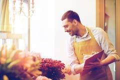 Kwiaciarnia mężczyzna z schowkiem przy kwiatu sklepem Obraz Stock