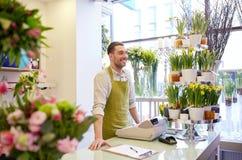 Kwiaciarnia mężczyzna z schowkiem przy kwiatu sklepu kontuarem Zdjęcia Royalty Free
