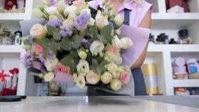 Kwiaciarnia pakuje bukiet od róż i liści w papierze, zbliżenie ręki zdjęcie wideo