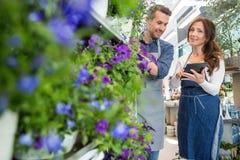 Kwiaciarnia Patrzeje Żeńskiego kolegi Używa Digital Zdjęcia Royalty Free