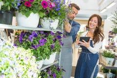 Kwiaciarnia Patrzeje Żeńskiego kolegi Używa pastylkę Fotografia Royalty Free